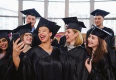 Grupo étnico multi de estudiantes graduados que toman el selfie imagen de archivo