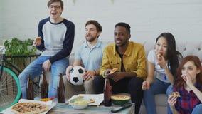 Grupo étnico multi de fans de deportes de los amigos que miran campeonato del fútbol en la TV junta que come la pizza y que bebe
