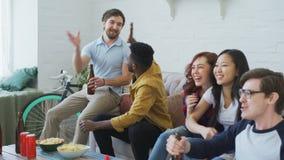 Grupo étnico multi de fans de deportes de los amigos que miran el acontecimiento deportivo en la TV juntos que come los bocados y almacen de metraje de vídeo