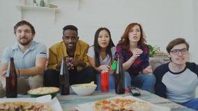 Grupo étnico multi de fans de deportes de los amigos que miran el partido de deporte en la TV junto que celebra meta del equipo p almacen de metraje de vídeo