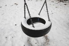 Grupo abandonado velho de balanços do pneu cobertos pela neve contra o fundo da paisagem da floresta do inverno Conceito das memó imagens de stock