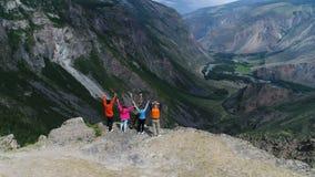 Grupo acertado de amigos felices en el top de la montaña, cámara lenta aérea 4k metrajes