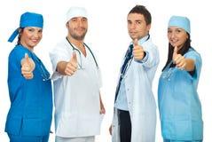 Grupo acertado de doctores que dan los pulgares Foto de archivo