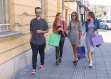 Grupo alegre de adolescentes que caminan después de hacer compras en ciudad Foto de archivo libre de regalías