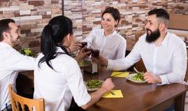 Grupo alegre de amigos en la tabla del restaurante Fotos de archivo