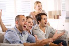 Grupo alegre de amigos que olham o fósforo de futebol Imagem de Stock