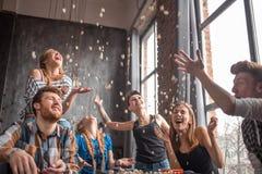 Grupo alegre de amigos que têm o divertimento em casa, comendo a pipoca e apreciando junto fotos de stock royalty free