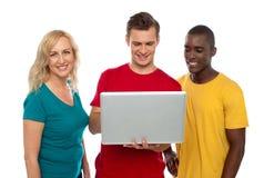 Grupo alegre de amigos que trabajan en la computadora portátil Foto de archivo libre de regalías