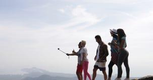 Grupo alegre de caminhada dos turistas em homens superiores e nas mulheres felizes guardando da câmera da ação da montanha que fa filme
