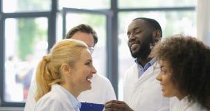 Grupo alegre de científicos que discuten resultados del descubrimiento acertado del experimento en raza sonriente feliz de la mez almacen de metraje de vídeo