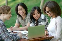 Grupo alegre de estudiantes jovenes que se sientan y que estudian Fotografía de archivo libre de regalías