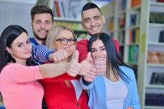 Grupo alegre de estudiantes que sonríen en la cámara con los pulgares para arriba, el éxito y aprendiendo concepto Imagen de archivo