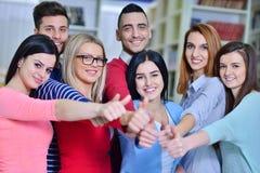 Grupo alegre de estudiantes que sonríen en la cámara con los pulgares para arriba, el éxito y aprendiendo concepto Fotos de archivo libres de regalías