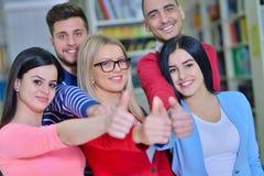 Grupo alegre de estudiantes que sonríen en la cámara con los pulgares para arriba, el éxito y aprendiendo concepto Foto de archivo libre de regalías