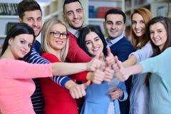 Grupo alegre de estudiantes que sonríen en la cámara con los pulgares para arriba, el éxito y aprendiendo concepto Imagen de archivo libre de regalías