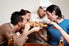 Grupo alegre de juventud en una pizza Imagen de archivo libre de regalías