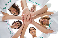 Grupo alegre de voluntários que unem as mãos Fotografia de Stock