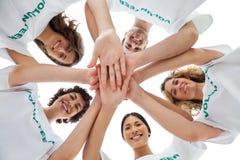 Grupo alegre de voluntarios que ponen las manos juntas Fotografía de archivo