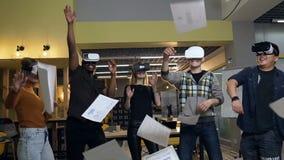 Grupo alegre dos trabalhadores de escritório nos vidros virtuais do vr que jogam o papel, documentos video estoque