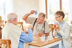 Grupo aposentado aposentado no jogo de cartas foto de stock
