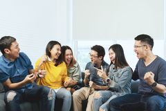 Grupo asiático atrativo novo de amigos que falam e que riem com o feliz em recolher a reunião que senta-se em casa fotos de stock royalty free