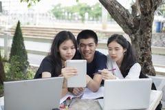 Grupo asiático de estudantes que usam a tabuleta e o caderno que compartilham com o t fotografia de stock royalty free