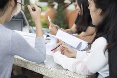 Grupo asiático de estudantes que usam a tabuleta e o caderno que compartilham com o t imagens de stock royalty free