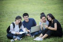 Grupo asiático de estudantes que usam a tabuleta e o caderno que compartilham com o t foto de stock royalty free