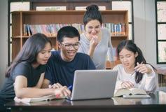 Grupo asiático de estudiantes que comparten con las ideas para trabajar en el th imagen de archivo
