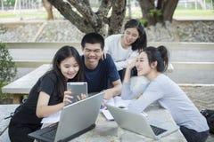 Grupo asiático de estudiantes que usan la tableta y el cuaderno que comparten con t Imagen de archivo libre de regalías
