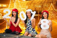 Grupo asiático joven de mujeres con la celebración de días festivos de la Navidad del sombrero de Papá Noel Foto de archivo