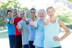 Grupo atlético feliz com polegares acima imagens de stock royalty free