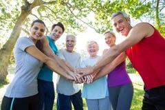 Grupo atlético feliz que pone sus manos juntas fotos de archivo