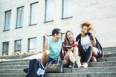Grupo bonito de teenages na construção da universidade com huggings dos livros, estilo de vida dos estudantes das nações da diver foto de stock