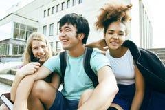 Grupo bonito de teenages na construção da universidade com huggings dos livros, estilo de vida dos estudantes das nações da diver imagens de stock royalty free