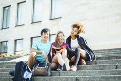 Grupo bonito de teenages na construção da universidade com huggings dos livros, estilo de vida dos estudantes das nações da diver fotos de stock royalty free