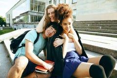 Grupo bonito de teenages na construção da universidade com huggings dos livros, estilo de vida dos estudantes das nações da diver imagens de stock