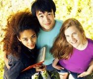 Grupo bonito de teenages na construção da universidade com livros Fotos de Stock Royalty Free