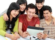 Grupo cómodo de estudiantes con PC de la tablilla Fotos de archivo