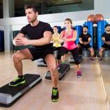 Grupo cardiio de la posición en cuclillas de la danza del paso en el gimnasio de la aptitud Fotografía de archivo