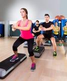 Grupo cardiio de la posición en cuclillas de la danza del paso en el gimnasio de la aptitud Imágenes de archivo libres de regalías