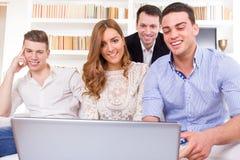 Grupo casual de amigos que se sientan en el sofá que mira el ordenador portátil Imagenes de archivo