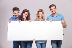 Grupo casual de gente joven que lleva a cabo a un tablero en blanco grande Imagen de archivo