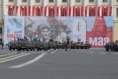 Grupo con las banderas en los coches UAZ-469 en el jefe de una columna del equipo militar Imágenes de archivo libres de regalías