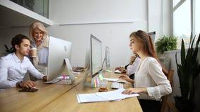 Grupo corporativo de los empleados que trabaja en los ordenadores de la PC en oficina junto almacen de metraje de vídeo
