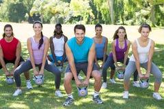 Grupo da aptidão que squatting no parque com sinos da chaleira Foto de Stock