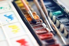 Grupo da arte de paleta do vintage de pinturas da aquarela em umas cubetas e em umas diversas escovas imagem de stock royalty free