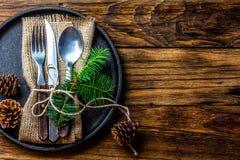 Grupo da cutelaria do vintage, decoração do Natal na placa do ferro, fundo de madeira Fotos de Stock Royalty Free
