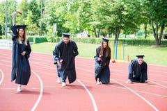 Grupo da graduação de estudantes que comemoram na trilha atlética, preparação imagem de stock