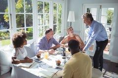 Grupo da interação executiva ao comer o café da manhã Foto de Stock